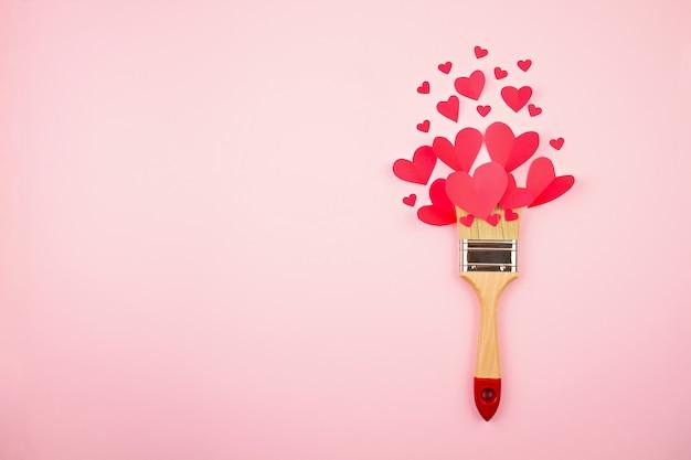 ピンクのパステル調の背景に紙の心とペイントブラシ。 Premium写真