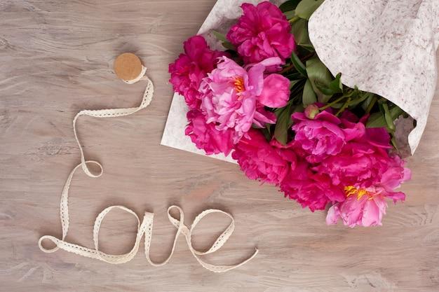 牡丹の花束と愛という言葉で形成されたリボン Premium写真