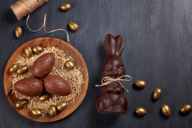 チョコレートの卵とウサギの木製の背景にイースター組成 Premium写真