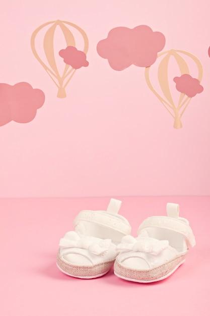 Детские милые розовые туфли на розовом пастельном фоне с облаками и шариками Premium Фотографии