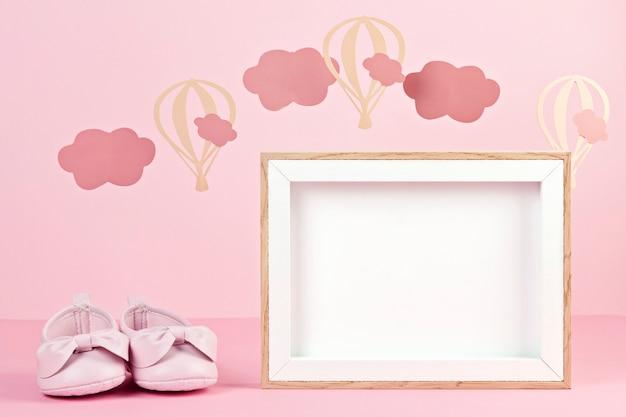雲と風船とピンクのパステル調の背景の上の女の赤ちゃんかわいいピンクの靴 Premium写真