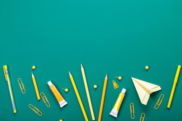 Желтые школьные принадлежности над зеленой доске. образование, обучение и обратно в школу Premium Фотографии