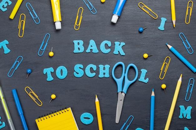 黒板の上にカラフルな文房具で学校のテキストに戻る Premium写真