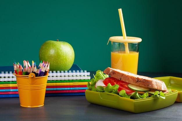 プラスチック製のお弁当箱でヘルシーなランチに新鮮なサンドイッチとリンゴ Premium写真