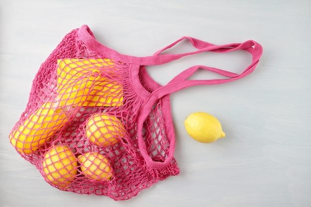 Многоразовая сетчатая сумка с лимонами, фруктами и стеклянной бутылкой Premium Фотографии