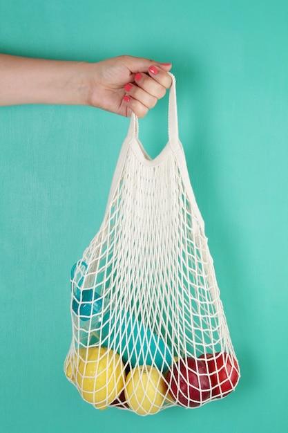 Многоразовая сумка с лимонами, фруктами и стеклянной бутылкой. ноль отходов, без пластика концепции. Premium Фотографии