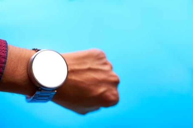 青い背景に手にスマートな時計 Premium写真