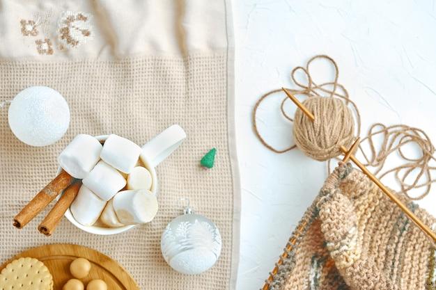 Горячий кофе с печеньем, зефиром, корицей, елочными украшениями и вязанием шарфа Premium Фотографии
