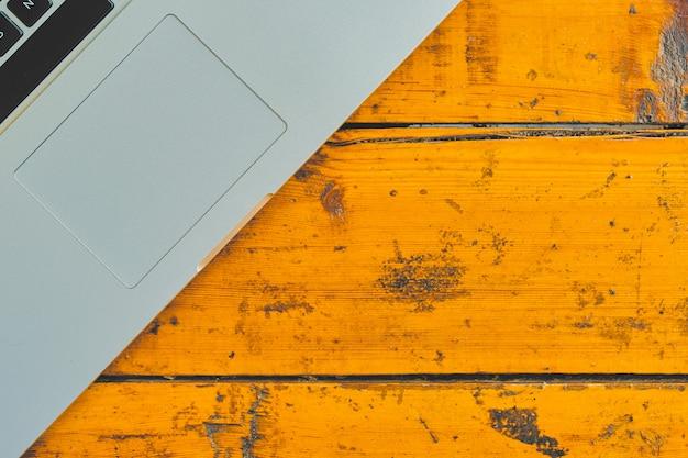 オフィスのテーブル背景にラップトップコンピューター。木製の卓上のノートブックの平面図です。 Premium写真