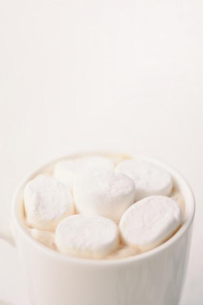 テーブルの上の白いマグカップでマシュマロとホットコーヒー。垂直クロップ Premium写真