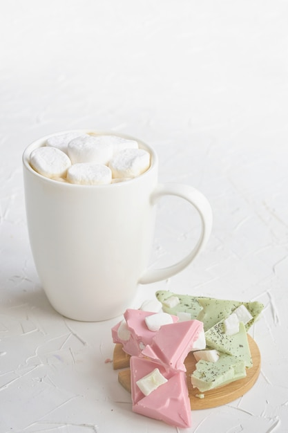 ライムとストロベリーチョコレートのテーブルの横にある白いマグカップでマシュマロとホットコーヒー Premium写真