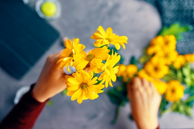 女性はロフトテーブルの上のガラスの透明な花瓶に黄色の菊の花を置く Premium写真