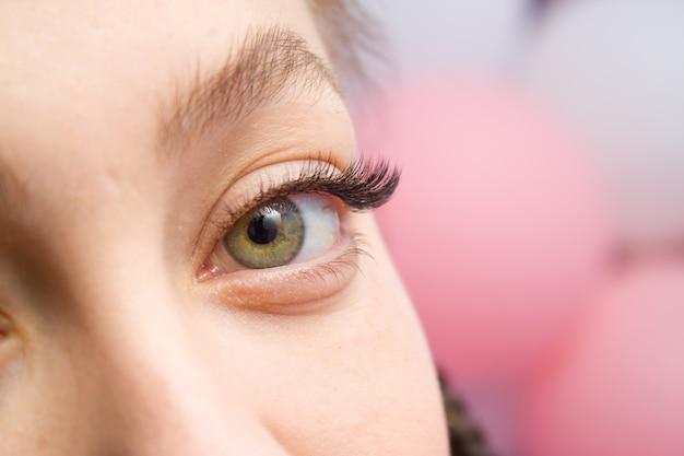 まつげエクステの手順。長いつけまつげを持つ女性の目。 Premium写真