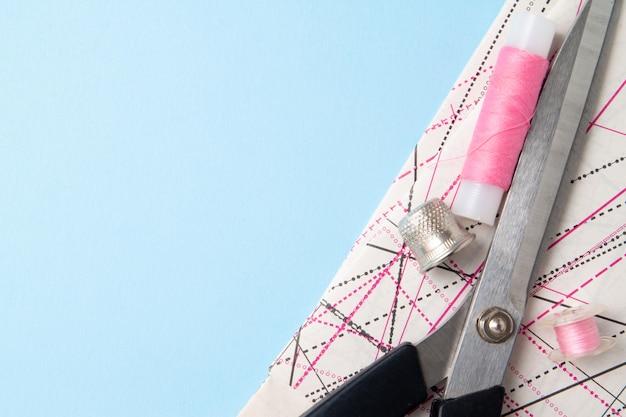 ピンクの糸のコイルとはさみのパターンと青の裁縫用アクセサリー Premium写真