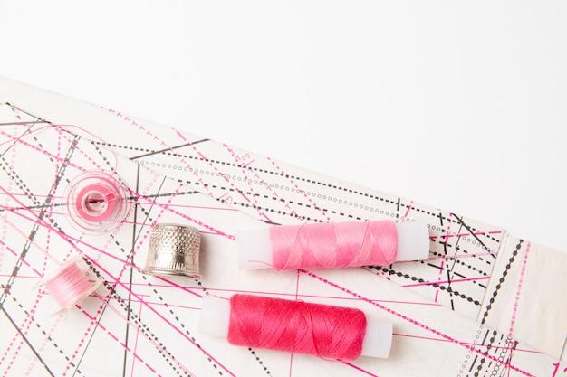 ピンクの糸コイルとパターンと白の裁縫用アクセサリー Premium写真