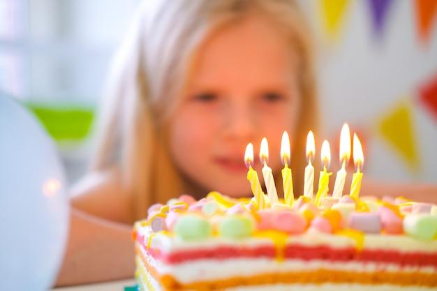 誕生日虹のケーキのろうそくを見て、誕生日パーティーでそれらを吹き消す前に願いを作る金髪白人少女。ろうそくに焦点を当てます。風船でカラフルな背景 Premium写真