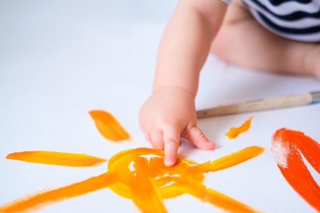 Ребенок ползает по полу, играя с красками Premium Фотографии