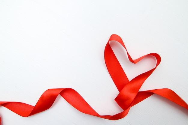 白い木製の背景に赤いリボンで作られたハート形 Premium写真