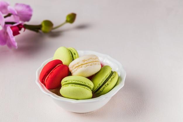 春の花、パステルカラーの明るい背景にマカロンまたはマカロンフランスのクッキー。 Premium写真