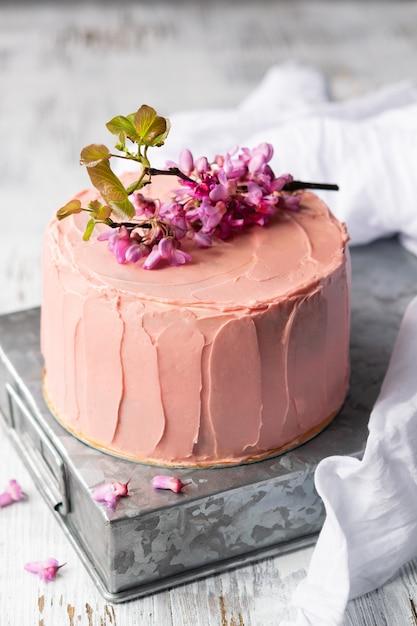 花で飾られたロマンチックなピンクのケーキ、結婚式、誕生日やイベント、母の日のための素朴なスタイル Premium写真