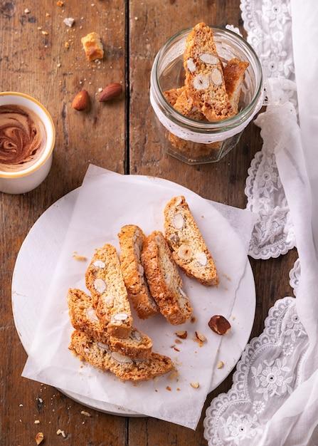 伝統的なペストリー、イタリアの自家製ビスコッティクッキーまたはカントゥチーニ、アーモンドナッツとコーヒー。 Premium写真