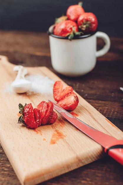 フルーツドライヤーラック用に準備された赤いスライスしたイチゴ。新鮮なイチゴをきれいにしてカット Premium写真