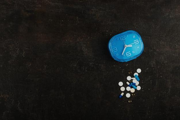 暗いテーブルに盛り合わせの丸薬と青い時計。健康薬物医学の概念 Premium写真