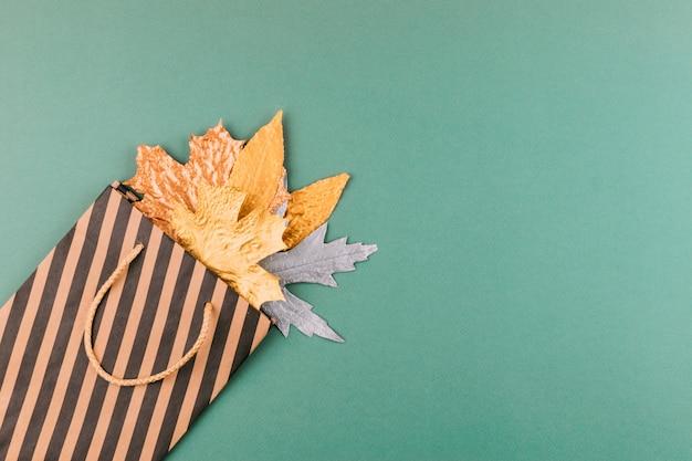 Осенняя композиция с золотыми листьями в подарочной сумке на фоне зеленой бумаги Premium Фотографии