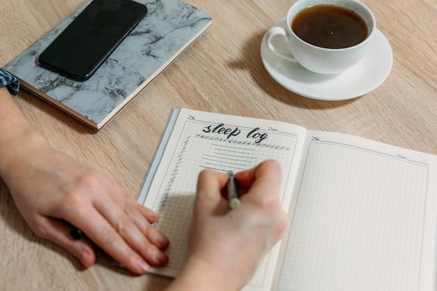 テーブルの上の睡眠ログまたは日記を持つ女性の手 Premium写真