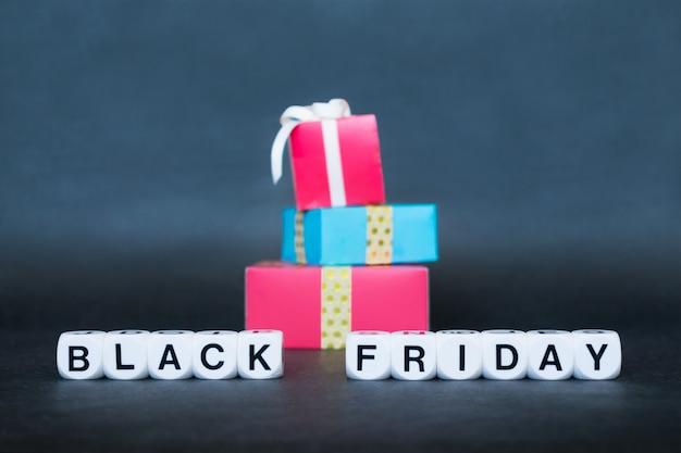 Продажа баннера с текстовым словом «черная пятница» и многоцветными подарочными коробками. Premium Фотографии