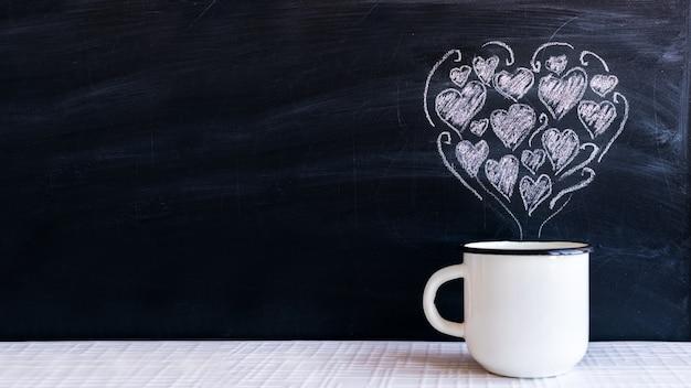 白い金属のカップとチョークで描かれた小さな心を心の形で Premium写真