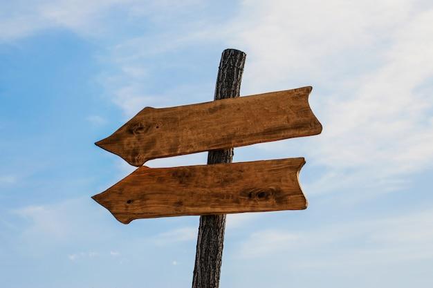 Два деревянных стрелка указатели макет на голубом небе Premium Фотографии