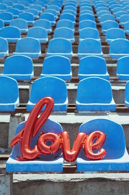 青いスタジアム席に赤いホイル風船が大好き Premium写真