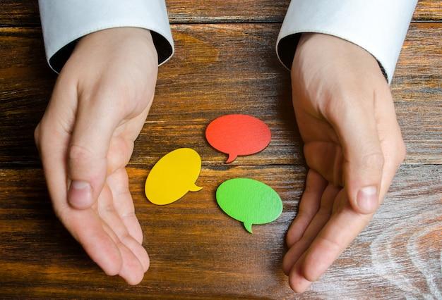 Мужчина собирает в руках разноцветные речевые пузыри. слушайте другие мнения Premium Фотографии