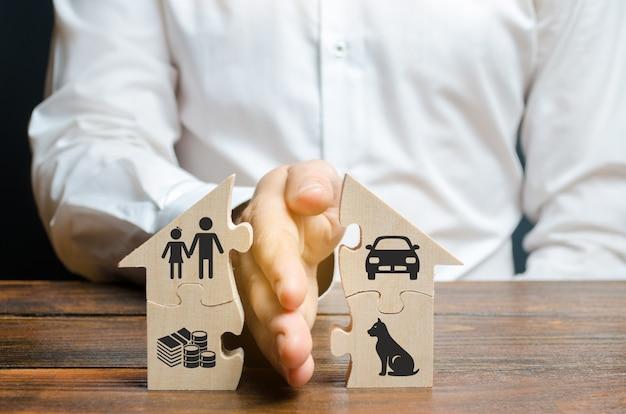 男は、財産、子供、ペットの画像を彼の手のひらに家を共有します Premium写真