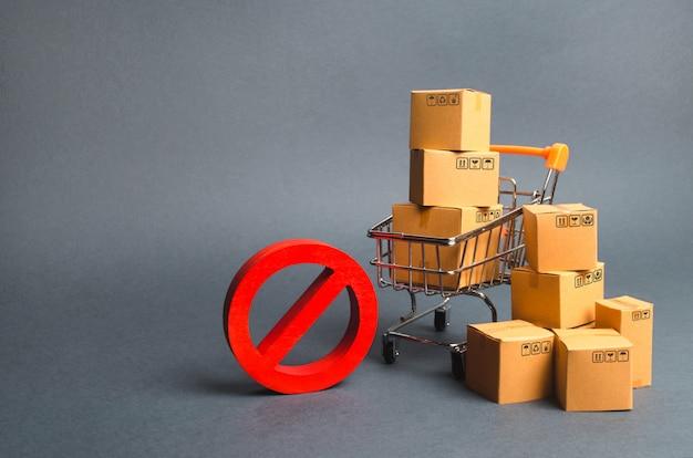 Картонные коробки, тележка супермаркета и красный символ нет. эмбарго, торговые войны. ограничение Premium Фотографии