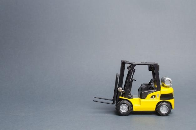 灰色の背景に黄色のフォークリフトトラックの側面図です。倉庫設備、車両 Premium写真