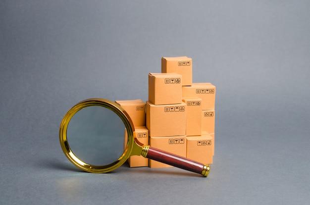 Куча коробок и увеличительное стекло. поиск концепции товаров и услуг. отслеживание посылок Premium Фотографии