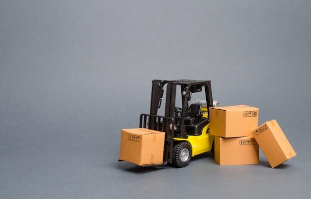 段ボール箱と黄色のフォークリフト。商品の売り上げ、生産を増やす。交通手段 Premium写真