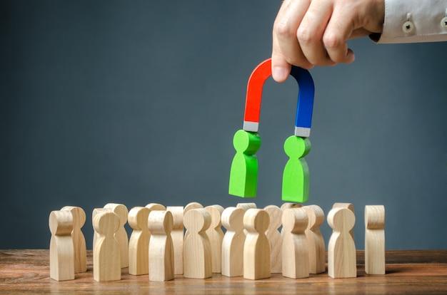 磁石を持ったビジネスマンは群衆の中から人々の緑色の数字を引き出します。新入社員の募集 Premium写真