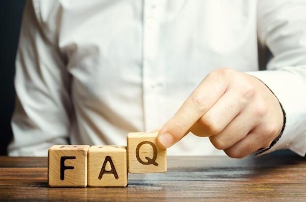 ビジネスマンは、よくある質問という言葉で木製のブロックを置く Premium写真