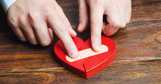 Мужчина склеивает красное сердце с гипсом. Premium Фотографии