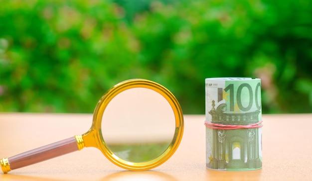 Банкноты евро и увеличительное стекло. Premium Фотографии