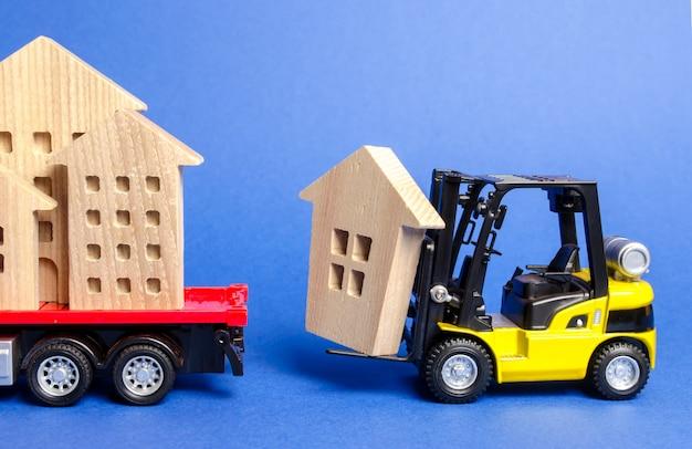 Желтый вилочный погрузчик загружает деревянную фигуру дома в грузовик. Premium Фотографии