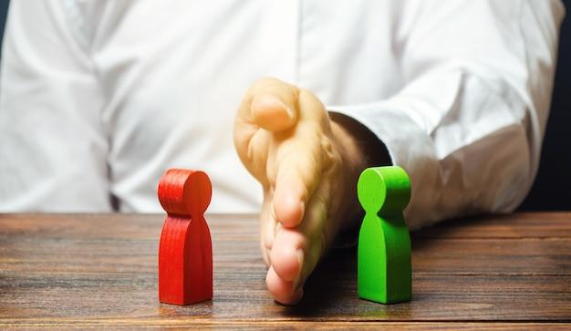 Человек делит ладонью красные и зеленые фигуры людей. Premium Фотографии