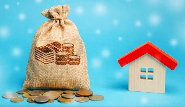 コインと雪で木造住宅とお金の袋。冬季の不動産市場。 Premium写真