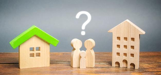 Два миниатюрных деревянных дома и семья между ними. Premium Фотографии