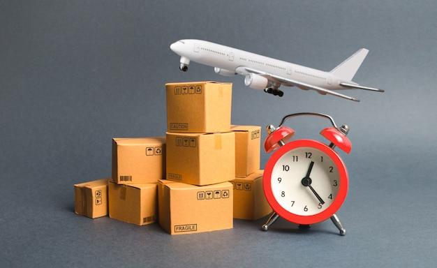 Грузовой самолет, стопка картонных коробок и красный будильник. концепция экспресс-доставки Premium Фотографии