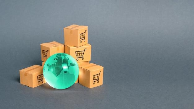 Синий стеклянный шар и картонные коробки. распределение и торговля товарами по всему миру Premium Фотографии