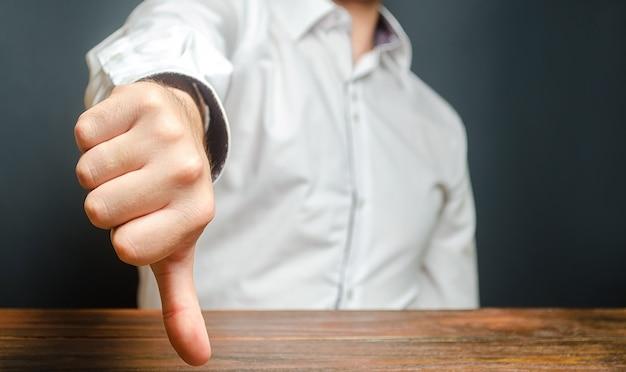 男は親指を下に示します。不承認と拒否のジェスチャー。悪い評価、厳しい批判 Premium写真
